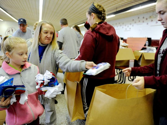 Darrin Phegley / The Gleaner Nancy Horn (second from left) and Ali Chandler. 9, (left) drop packages of socks and t-shirts in bags as volunteers prepare for the annual Goodfellows Christmas Party at South Middle School Saturday morning, December 20, 2014.