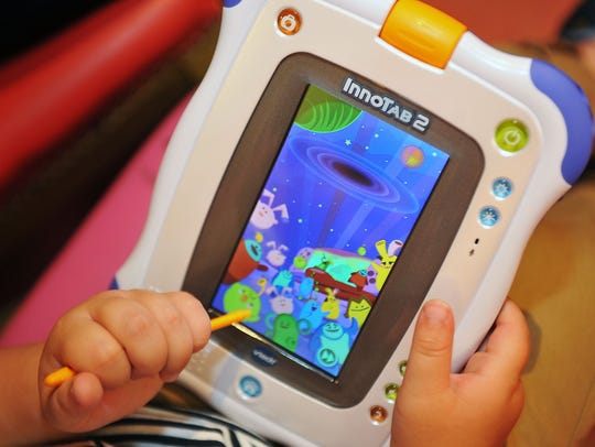 A child plays with a LeapPad2 Explorer.