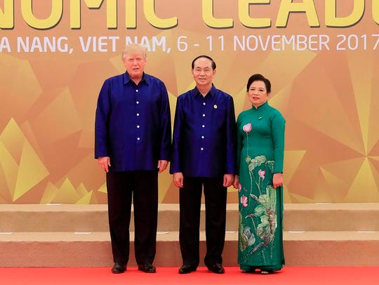 President Donald Trump poses with Vietnam President Tran Dai Quang and his wife, Nguyễn Thị Hiền, upon arrival for the Asia-Pacific Economic Cooperation Summit leaders gala dinner in the central Vietnamese city of Danang on Friday.