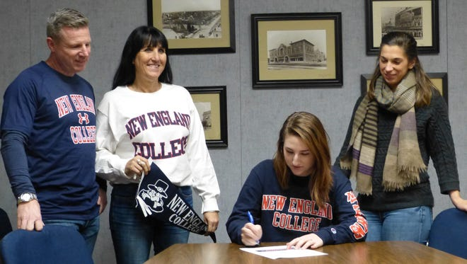 Red Bluff High senior Kennedy Somavia (second from right) signs Wednesday to play volleyball for New England College in New Hampshire in front of parents Troy and Lisa Somavia, and high school coach Kelli Mustaine.