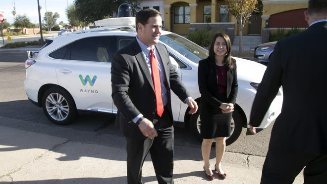 Gov. Doug Ducey and Jennifer Haroon, director of operations for Waymo, in front of a self-driving car, after Ducey took a ride in it in Chandler on  Dec. 15, 2016.
