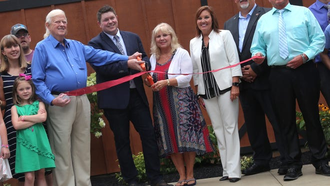 Jimmy Landoll (in suit, center), the general manager of  Landoll's Mohican Castle in Loudonville, cuts the ribbon to open the new 14-suites complex on Friday.