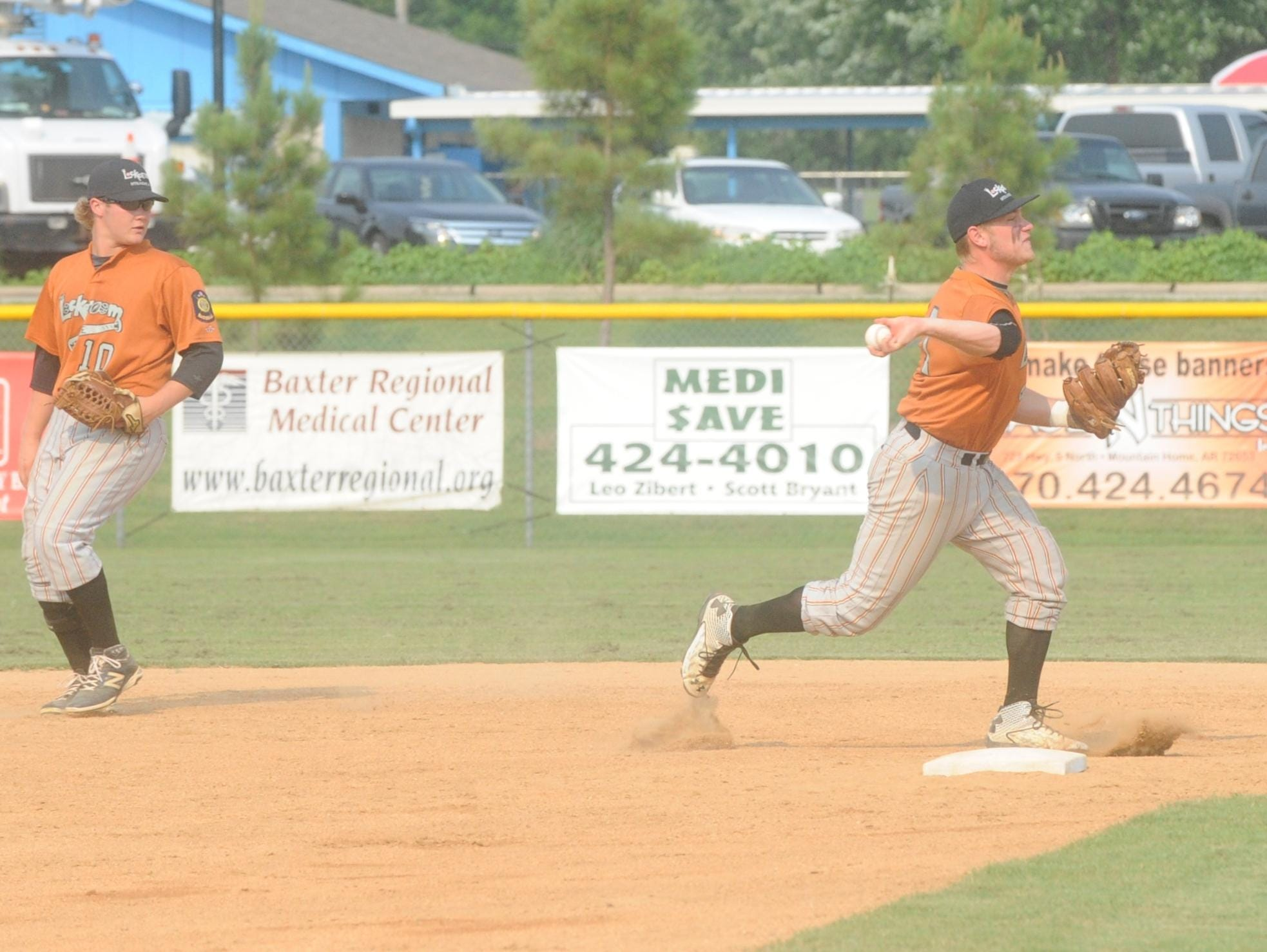 Lockeroom shortstop Hayden Hall, right, throws to first for an out during Mountain Home's 8-1 victory over Batesville on Tuesday at Cooper Park. Also pictured is second baseman Matt Robbins.