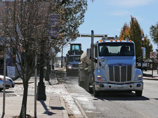 Heavy trucks on Tuesday move northbound  along Main Avenue in Aztec.