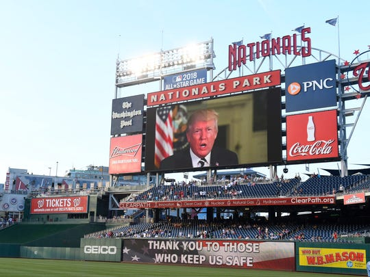 President Donald Trump on the big screen delivers a