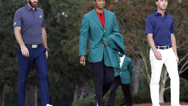 Tiger Woods (center) walks out with Dustin Johnson (left) and Andy Ogletree for the green jacket ceremony and trophy presentation after the final round of the Masters Tournament on Sunday.