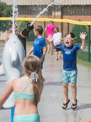 Colin Schlosser, 5, right, taunts the kids shooting the water cannons to squirt him during the grand opening of the new Dolphin Island Splash Pad at Sunset Kids Park in Gulf Breeze on Wednesday, May 30, 2018.