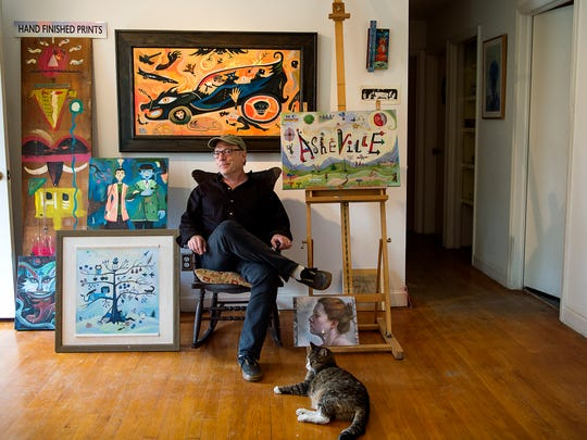 Andy Levine, an artist who works under the name John Nebraska, sits in his living room and studio surrounded by his artwork and cat in his Haw Creek home.