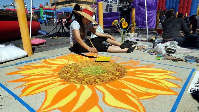 Artist Ali Rangel worked on her giant Sunflower chalk art during Chalk the Block in Downtown El Paso in 2016.