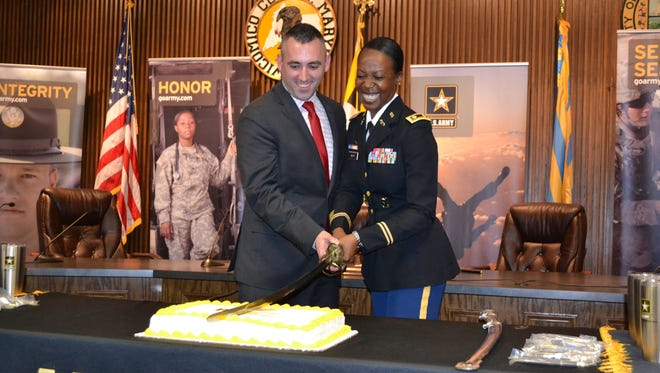 Salisbury Mayor Jake Day and Lt. Col. Vanessa Moye cut a cake after signing an agreement with the Partnership for Youth Success on Tuesday, Feb. 27.