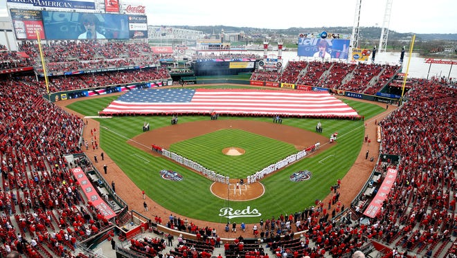 The National Anthem is sung as the American Flag is draped on the field during the Cincinnati Reds Opening Day pregame ceremony at Great American Ball Park Monday April 3, 2017.