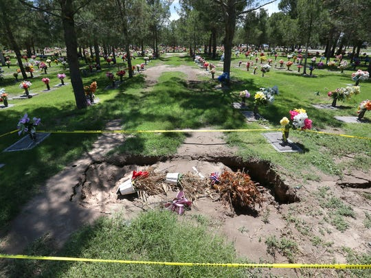A gravesite is taped off Tuesday at Mount Carmel Cemetery in the Lower Valley after heavy rains caused dozens of graves to sink.