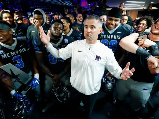 Memphis head coach Mike Norvell, middle, chats with