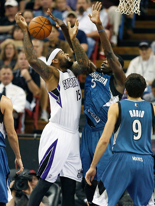 Sacramento Kings center DeMarcus Cousins (15) battles under the basket against Minnesota Timberwolves Gorgui Dieng (5) during the first half of an NBA basketball game in Sacramento, Calif., on Sunday, April 13, 2014.(AP Photo/Steve Yeater)