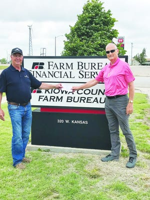 Kansas Farm Bureau member Scott Sparke (left) gives a check to Kiowa County Food Bank representative Jeff Blackburn. The financial donation will go towards feeding those in need in Kiowa County.