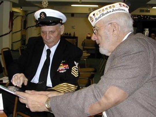Will Lehner (right) shows fellow World War II veteran Harry Alvey photos from his recent visit to Pearl Harbor while discussing the possibility of America waging a new war, 61 years after the Japanese attack on Hawaii.