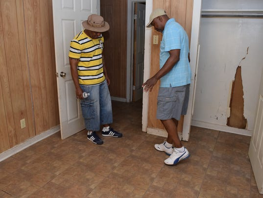 Luther Smith (right) shows Michael Smith how the foundation of the rental house Luther owns to has shifted due to flooding that occurred  twice in the past two years. He says two feet of water got in the house this last time and the water marks are visible. The ditches that ring the house have overflowed.