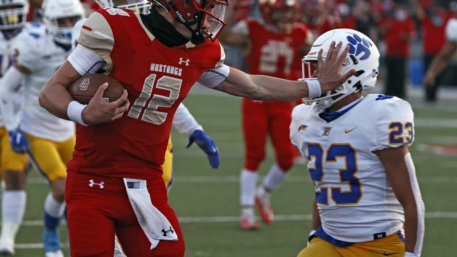 Coronado's Sawyer Robertson (12) stiff-arms Frenship's Stefano Sanchez (23) while scoring a touchdown during a nondistrict game Friday at PlainsCapital Park at Lowrey Field. Robertson threw for 416 yards and recorded five total touchdowns.
