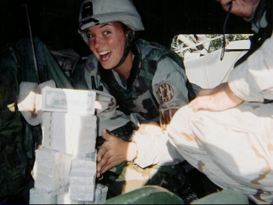 Laura Colbert, a Waupaca native, served in Iraq with the Wisconsin National Guard in 2003 and 2004. She's seen here with money being escorted to pay Iraqis