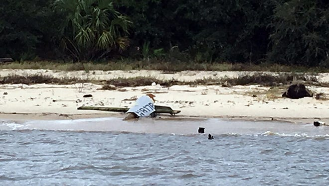 Debris from what authorities say appear to be a single-engine plane that went missing shortly after taking off from a nearby airport with three people aboard the day before rests on a beach, Tuesday morning , Oct. 27, 2015, near Ocean Springs, Miss. The plane had been bound for South Carolina, but it was less than 50 miles east of the Gulfport-Biloxi International Airport when it lost radar contact Monday afternoon.
