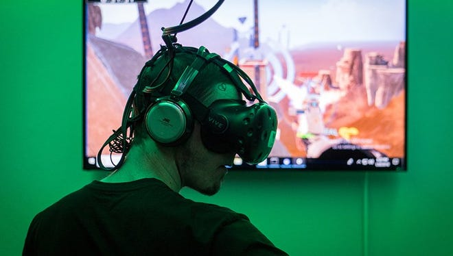 """Tyler Powell, a first-time VR player, paid a dollar per minute to use the VR Junkies' HTC Vive headset and fully immerse himself in """"Skyfront"""" with his friends."""