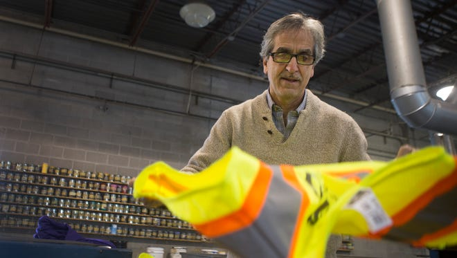 Vic Ciaccia makes a pile of safety vests after they have been screen printed at AVS Activewear on Thursday, February 19, 2015. Vic is a co-owner of the screen printing company, along with his brother, Tony.