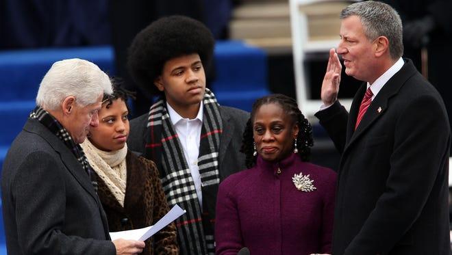 Chirlane McCray (2nd from right) standing beside her husband Mayor Bill de Blasio as he is sworn in on Jan. 1, 2014. (file photo)