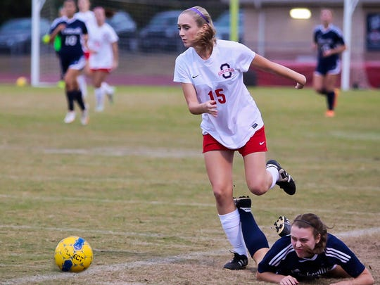 Oakland's Jenna Clothier runs past a Cookeville defender to gain possession of the ball.