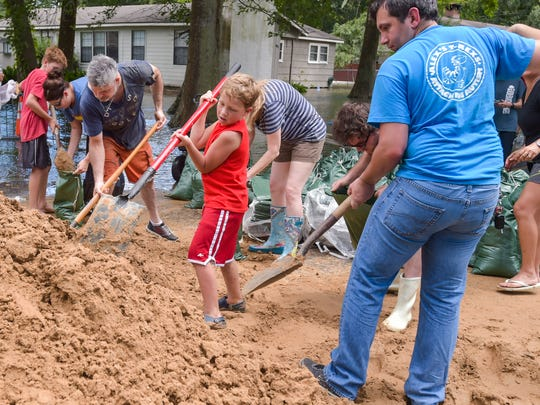 Volunteers pitch in to help residents along River Road near Oakbourne as the Vermilion River spills over the top of levee Monday.