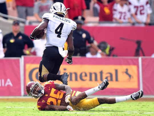 Jack Jones (25) of the USC Trojans misses a tackle as Darius Phillips (4) of the Western Michigan Broncos returns a kickoff for a touchdown to tie the score 28-28 during the fourth quarter at Los Angeles Memorial Coliseum on September 2, 2017.