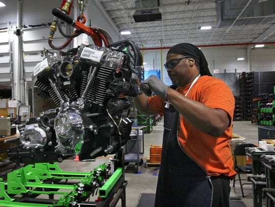 Michael Guster inspects and readies a new Harley-Davidson