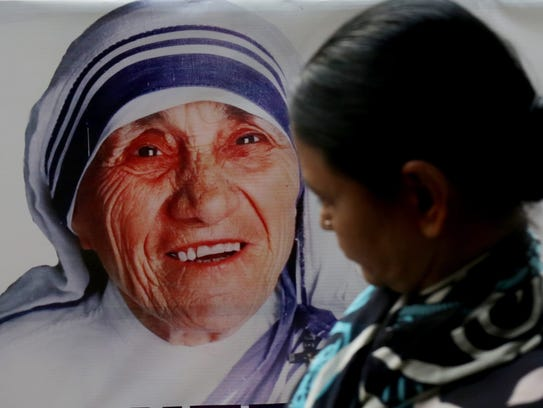 A commuter walks past a picture of Mother Teresa on