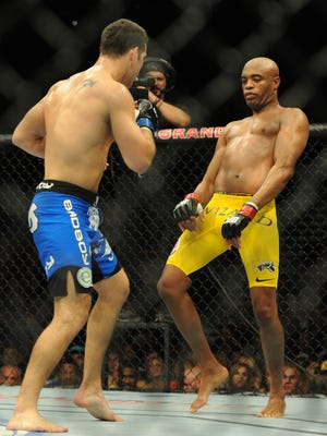 Chris Weidman, blue shorts, defeated Anderson Silva (yellow shorts) in the second round byTKO in July in their first UFC middleweight title fight.