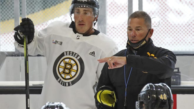 Bruins coach Bruce Cassidy, right, directs a drill as Brad Marchand listens during practice last week. Cassidy had to cancel a scrimmage Saturday because so many players were absent.