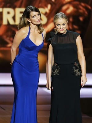 Tina Fey and Amy Poehler speak onstage at the Emmys on Sept. 22 in L.A.