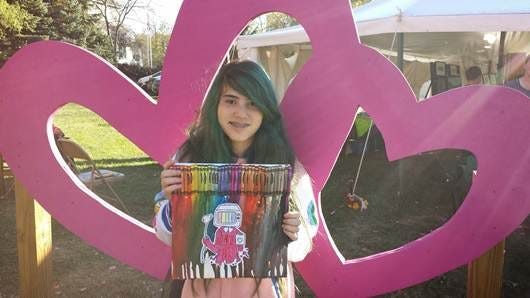 Natalie Garcia, 11, holds her wax crayon painting that is on display in New Paltz.