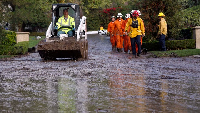 Work crews finish up cleaning a mud flow at a home in the suburb of Glendora, Calif., on Nov. 21.  More rain and snow could trigger mudslides this week in Southern California.