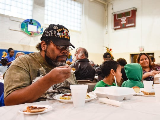 Matthew Bullock eats his meal with his two songs during the Thanksgiving meal held at the Marion Recreation Center on Wednesday morning.