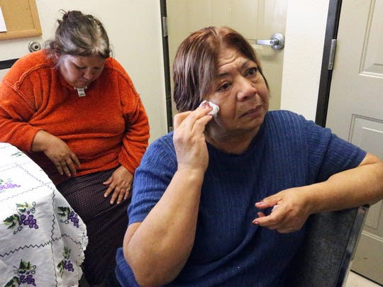 Carmen Rangel sheds tears as she recounts how she ended up in El Paso and a resident of one of the Opportunity Center's shelters Monday. Behind her is fellow resident Josefina Bardget.