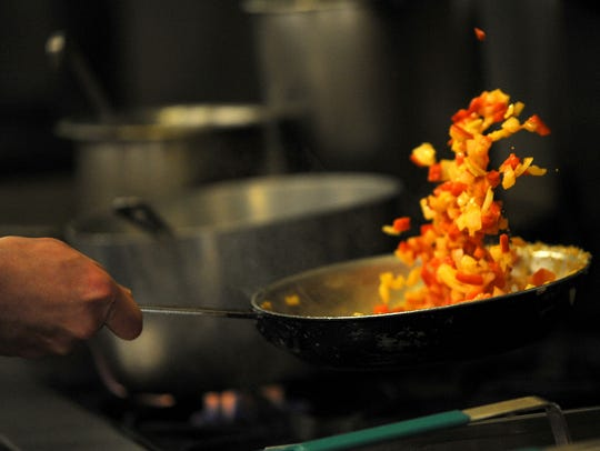 A Sonny Lubick Steakhouse chef tosses red pepper and