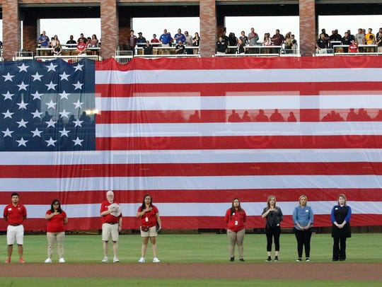 A giant U.S. flag is unfurled from the outfield seats
