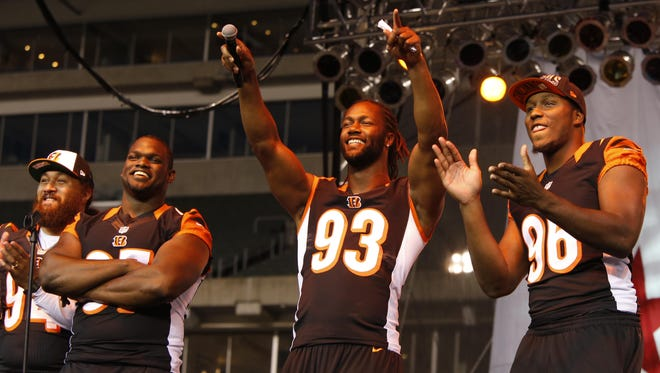 (Left to right:) Bengals defensive linemen Domata Peko, Geno Atkins, Michael Johnson and Carlos Dunlap work the crowd during a pep rally to kick off the team's 2013 training camp. All four players are still with the Bengals after Johnson re-signed on Sunday.