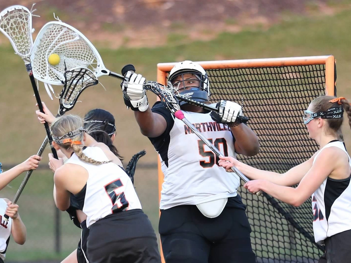 Northville goalie Gabby Goree (middle) makes a save late in the match surrounded by fellow defenders Paige Chapman (5) Shayla Crouteau (37) Anastasia Heath-Sheppard (9) in Friday's 13-6 win over Harrison.