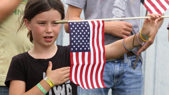 A 4-H member stands during the Pledge of Allegiance during the Warren County Fair Veterans Recognition program on July 25, 2015, in Indianola.