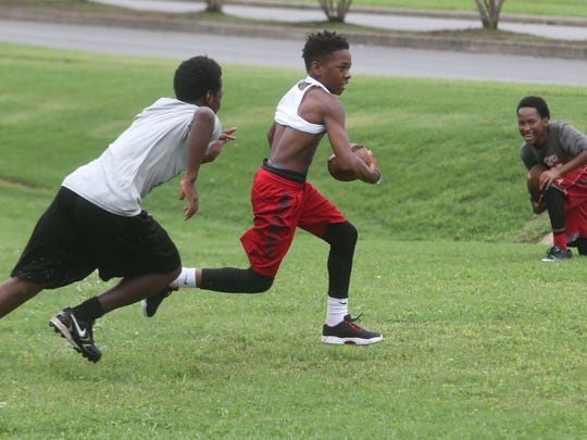 Whitworth Buchanan student Kendell Martin, 13, runs past a defender during Thursday's football camp at Patterson Park Community Center.
