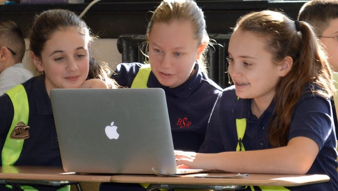 (From left) Corinne Vicente, Emma Fehrenbach and Caroline Bernhardt, students at Bishop Schad Regional School in Vineland, work together using a computer.