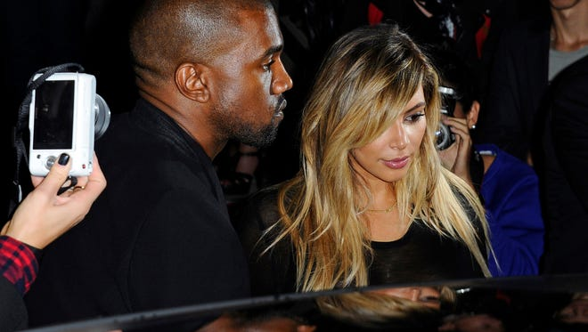 In this Sept. 29, 2013 file photo, Kanye West, left, and Kim Kardashian leave after attending Givenchy's ready-to-wear Spring/Summer 2014 fashion collection in Paris.