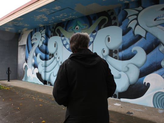 Peg Johnston looks at a mural she helped coordinate