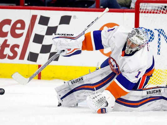 New York Islanders goaltender Thomas Greiss blocks a shot from the Carolina Hurricanes during the first period of an NHL hockey game Friday, Feb. 16, 2018, in Raleigh, N.C. Greiss had 45 saves in the team's 3-0 win. (AP Photo/Karl B DeBlaker)