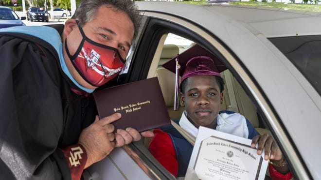 Palm Beach Lakes High School Principal David Alfonso poses for a photo with Treyvaughn Dobbs after the senior picked up his diploma in the school parking lot in West Palm Beach on Thursday.